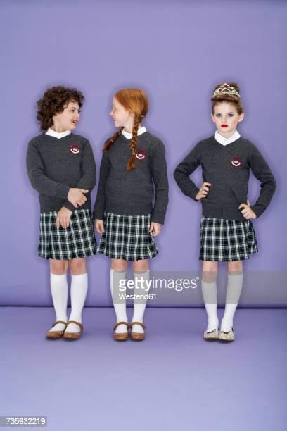 Three girls wearing school uniform