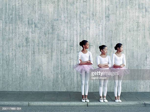 Three girls (10-12) wearing tutus in a row on pavement, arms crossed