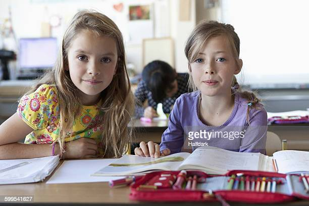 Three girls with books in classroom