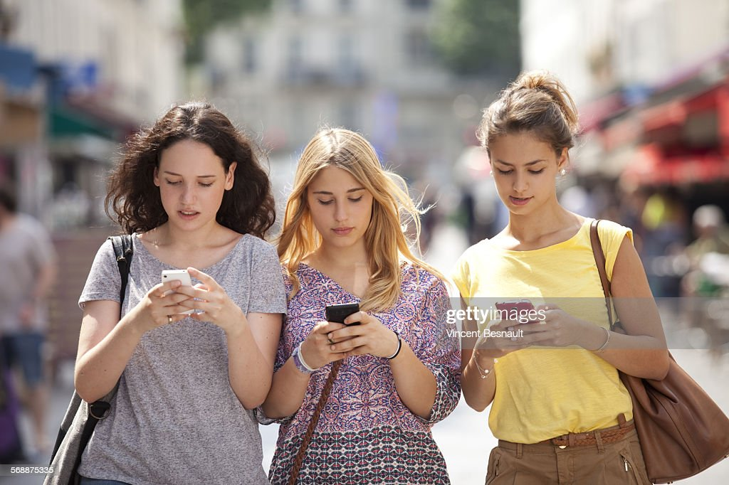 Three girls with their mobile phone : Stock Photo