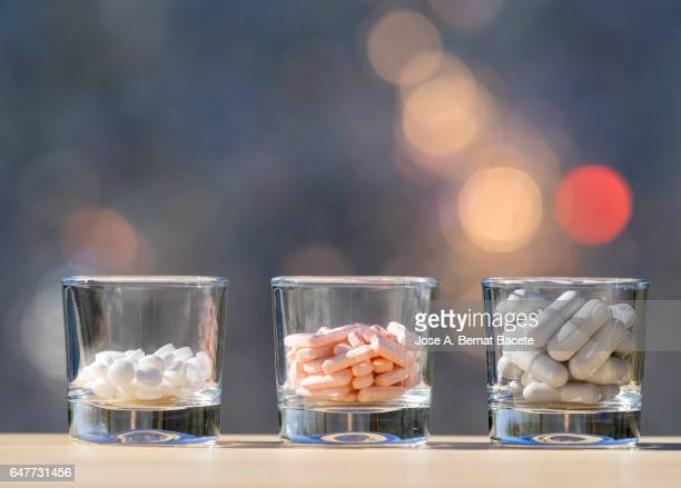 Three glass glasses with dangerous overdose of different medicines , illuminated by the light of the Sun