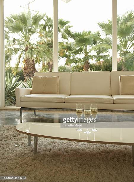 Three glasses of champagne on coffee table in living room