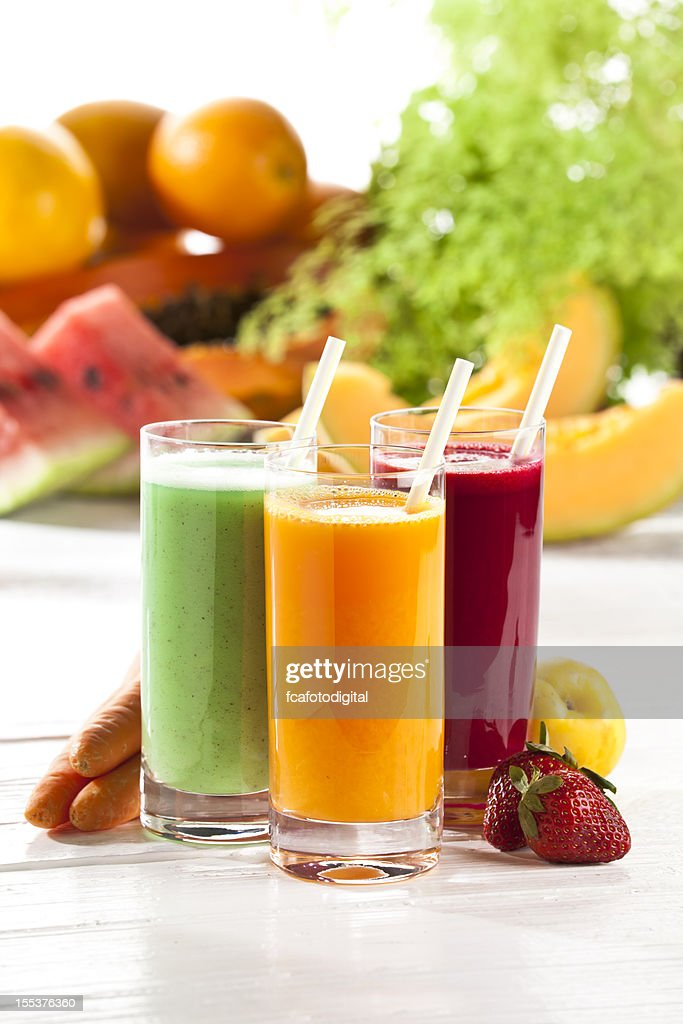 Three glasses of fruit juice with fruits in the background : Stock Photo