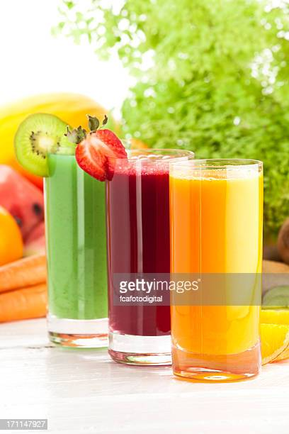 Three glasses of fruit juices on white garden table