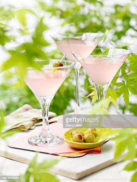 Three glasses of pink grapefruit and martini cocktails with green olives