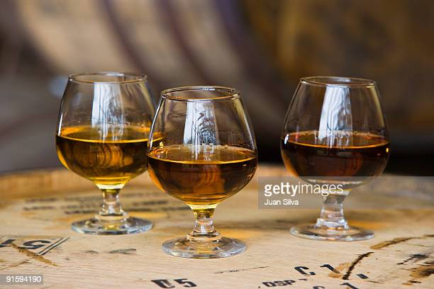 Three glasses of rum on barrel in warehouse