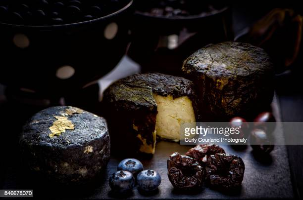 Three goat cheeses chevre in various coating: (charcoal or ash, nettle leaves, grape leaves) with blueberries, prunes, olives and figs, served on the black slate board
