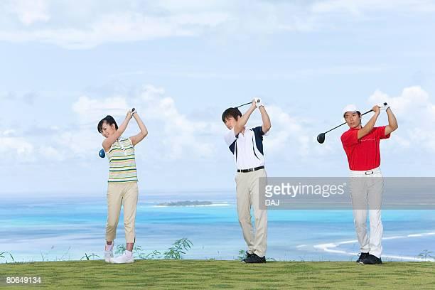 three golfers practicing shot, side by side, saipan, usa  - ゴルフ選手 ストックフォトと画像