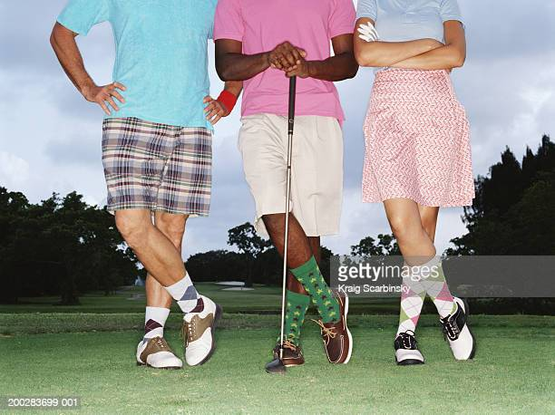 three golfers standing in row on golf course, low section - arms akimbo stock pictures, royalty-free photos & images