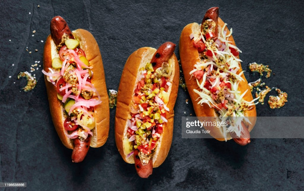 Three gourmet hot dogs on black background : Stock Photo