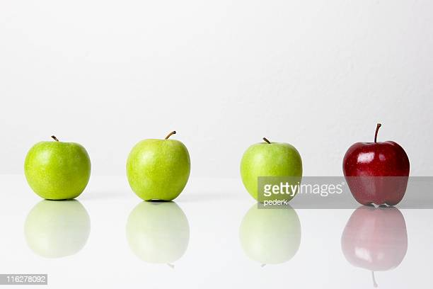 Three green apples and one red on white