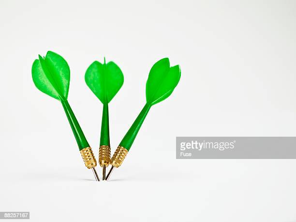 Three Green Darts Stuck Upright Close Together