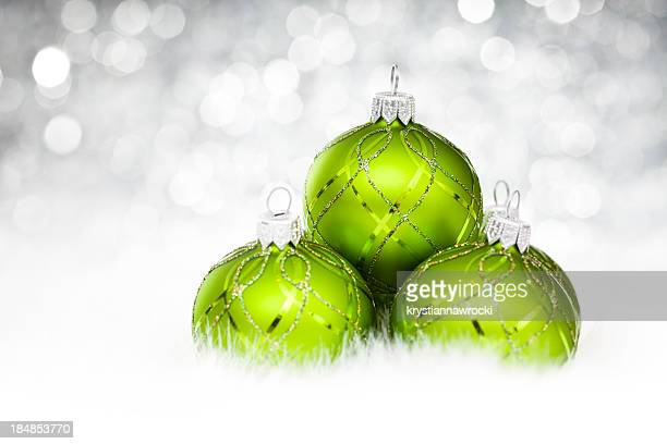 Three green holiday baubles stacked on white