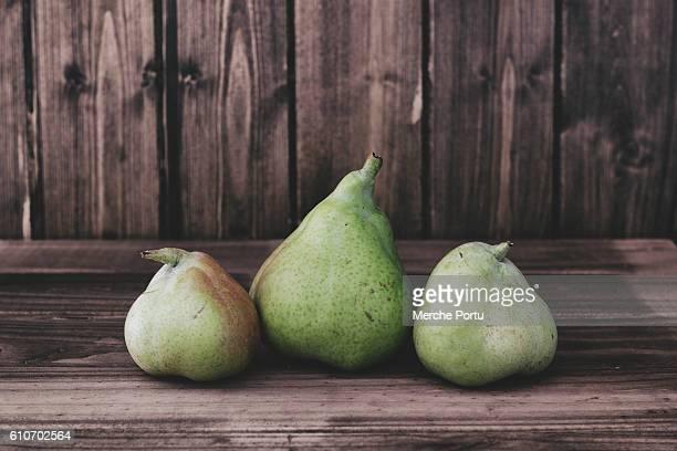 three green pears on rustic wooden table - san juan fotografías e imágenes de stock