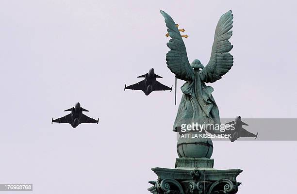 Three Gripen JAS39 type aircrafts of the Hungarian Air Force fly over the statue of the Gabriel archangel to honour new officers of the Hungarian...