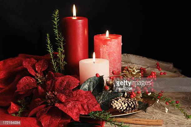 three grouped christmas candles standing among garlands - christmas star stock photos and pictures