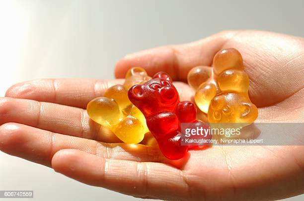 Three gummi bears in someones hand