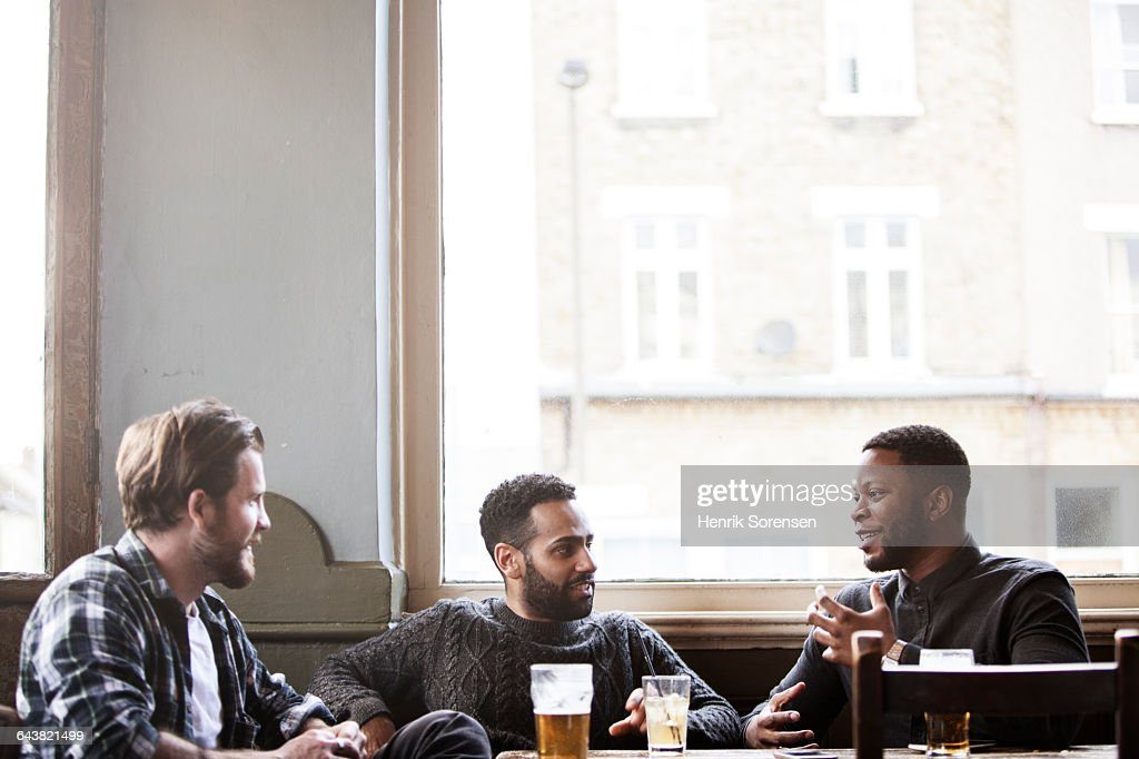 Three guys at a pub, one of the telling a story, while the two others are listening