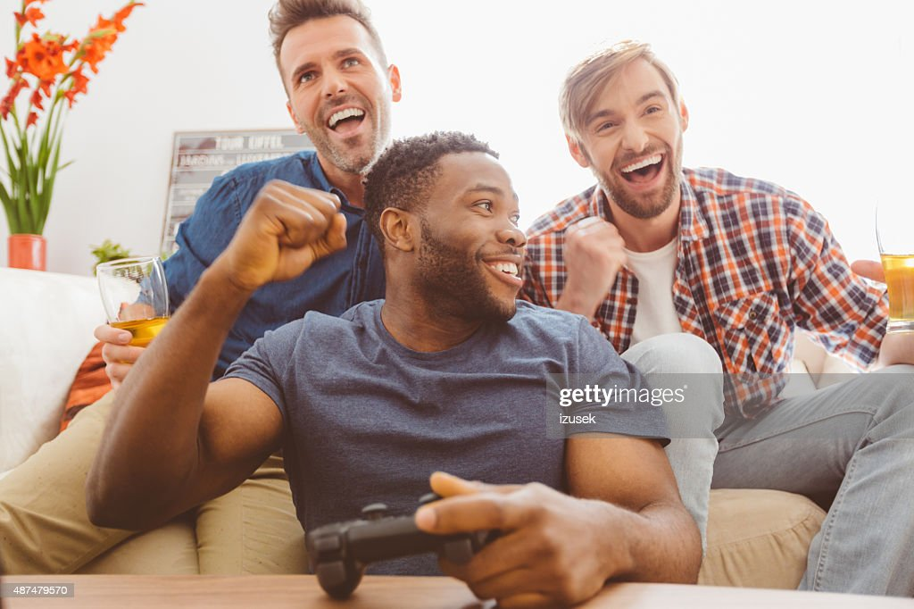 Three guys playing video games : Stock Photo
