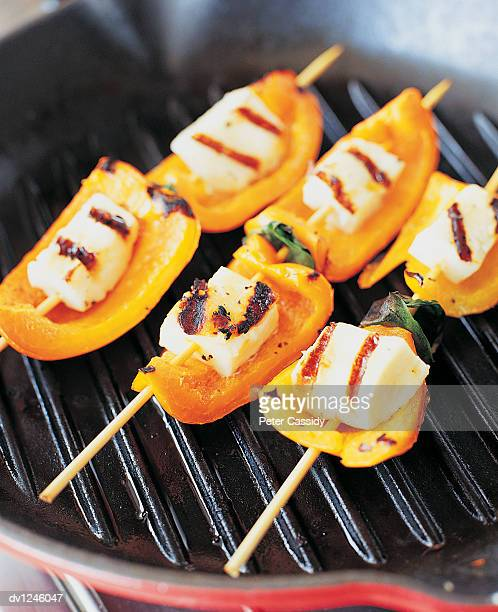 Three Halloumi and Yellow Pepper Kebabs Being Grilled