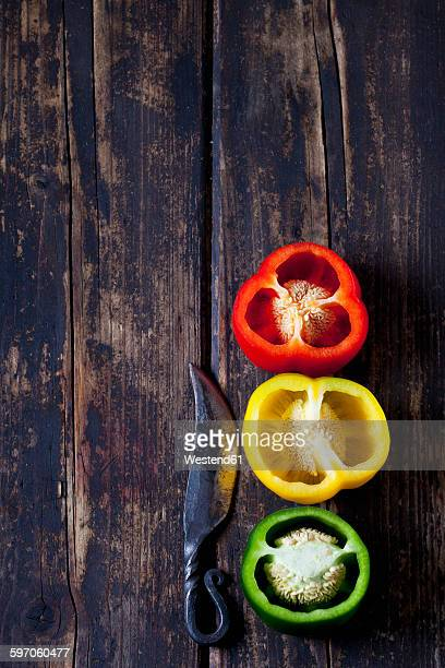 three halves of red, yellow and green bell pepper and a knife on dark wood - scharfe schoten stock-fotos und bilder