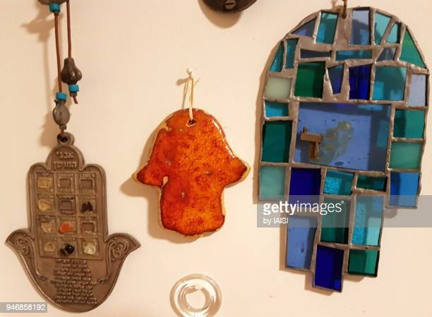 three hamsa symbols, in metal, terracotta, blue vitrail glass - hand of fatima stock photos and pictures