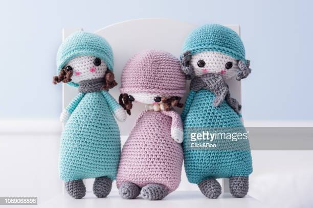 Three handmade crocheted dolls in blue with scarf and hat on a white chair.