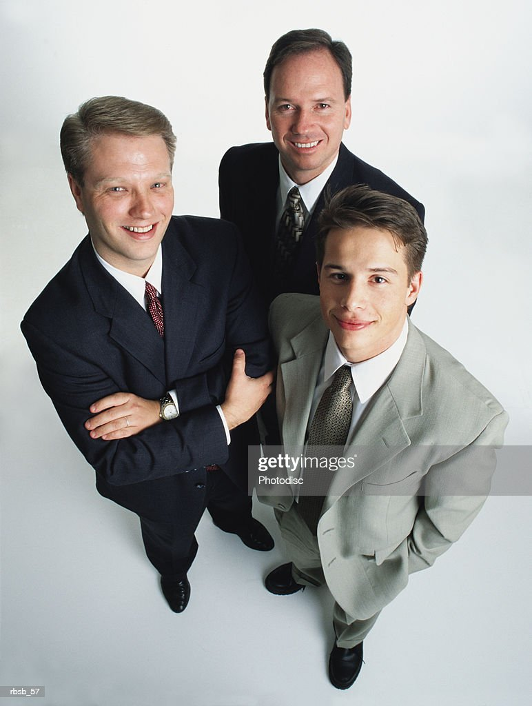 three handsome caucasian men in business suits looking up into the camera : Foto de stock