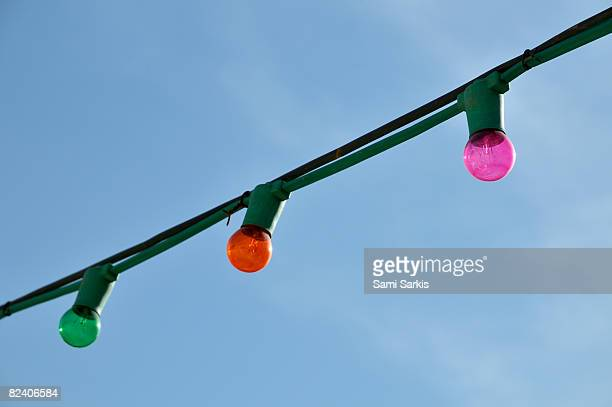 Three hanging colorful light bulbs