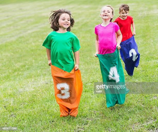 Trois enfants heureux dans la course en sac de pommes de terre
