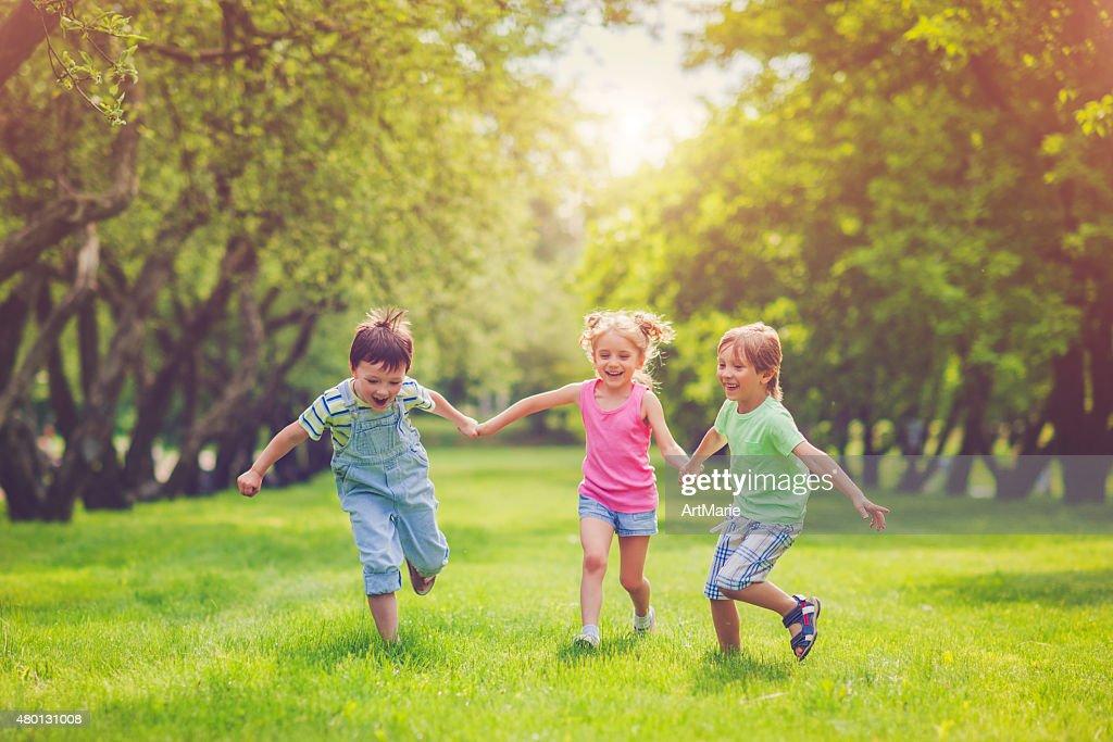 Three happy children in summer : Stock Photo
