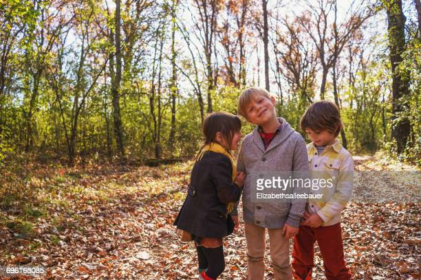 Three happy children playing in the woods