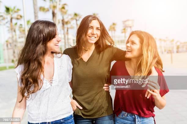 three happy female friends strolling on the boardwalk - 3人 ストックフォトと画像