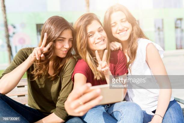Three happy female friends taking a selfie outdoors