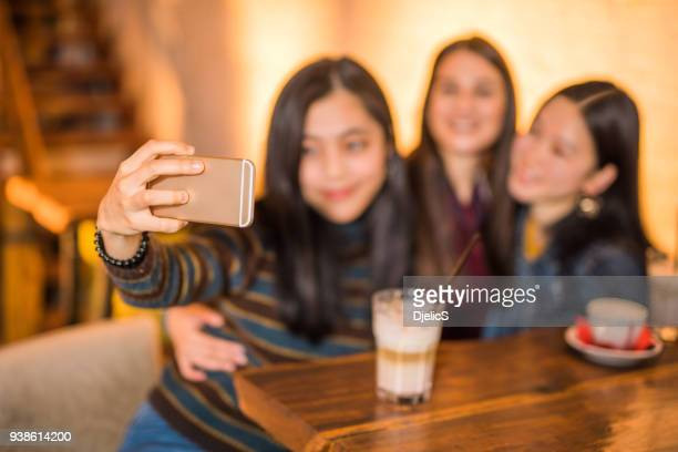 three happy female friends taking a selfie together in cafe. - korean teen stock pictures, royalty-free photos & images