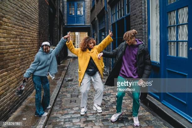 three happy friends dancing together in the city - dancing stock pictures, royalty-free photos & images