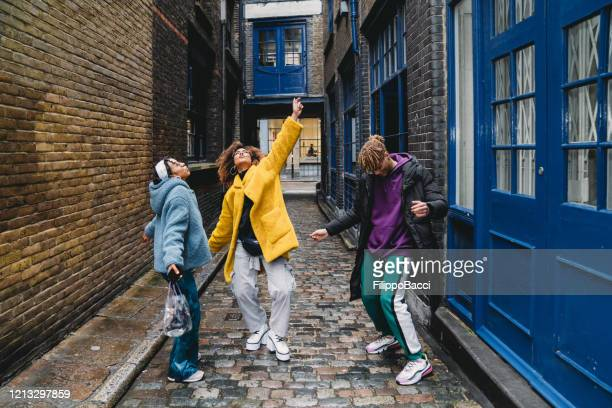 three happy friends dancing together in the city - cool attitude stock pictures, royalty-free photos & images