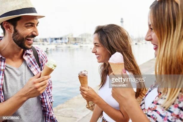 three happy friends holding ice cream cones - eis essen stock-fotos und bilder