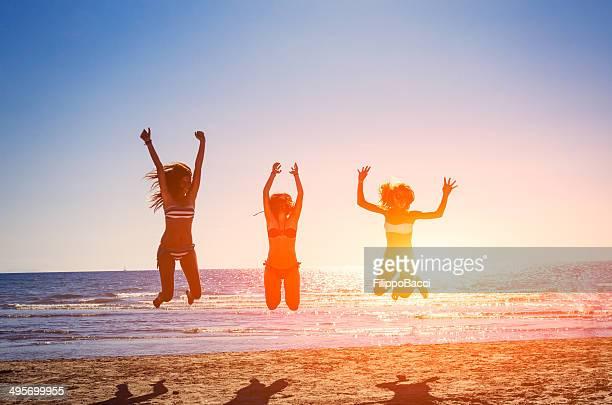 Três felizes amigos saltar na praia de Verão