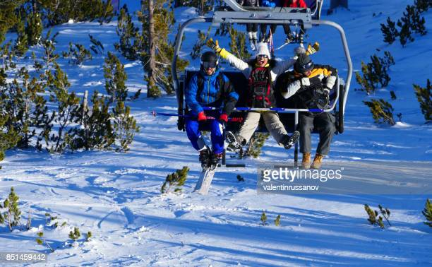 three happy friends riding a ski lift in the mountains - bansko stock pictures, royalty-free photos & images