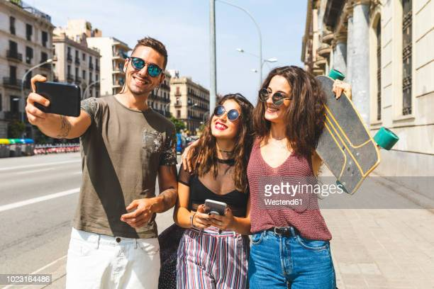 three happy friends taking a selfie in the city - nice girls pic stock photos and pictures