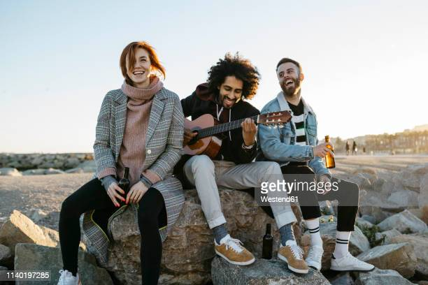 three happy friends with guitar sitting outdoors at sunset - músico fotografías e imágenes de stock
