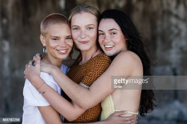 three happy girlfriends embracing - tre persone foto e immagini stock