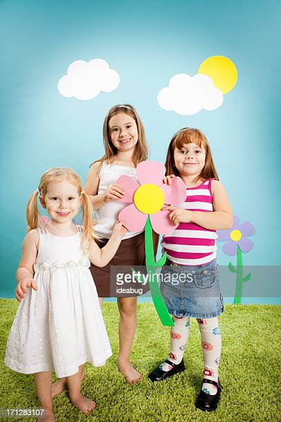 Three Happy Girls Holding Oversized Flower in Whimsical World