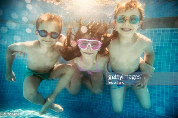 Three happy kids playing underwater