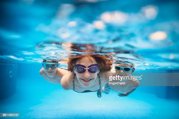 three happy kids swimming underwater in pool - piscina foto e immagini stock