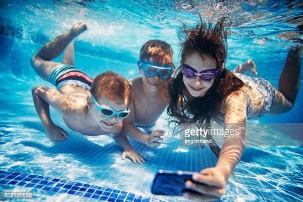 Three happy kids taking selfies underwater
