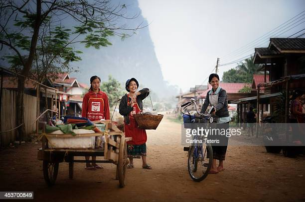 Three happy local women in Nong Khiew, Northern Laos coming home from market along the dirt main street of town with baskets a bike and a cart full...