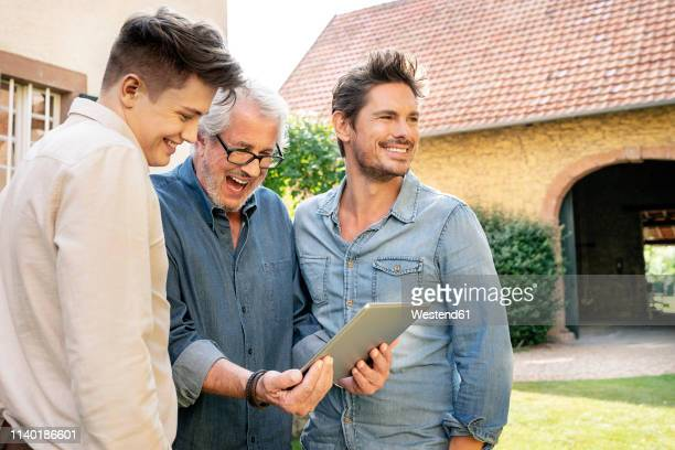 three happy men of different age using tablet in garden - small group of people stock pictures, royalty-free photos & images