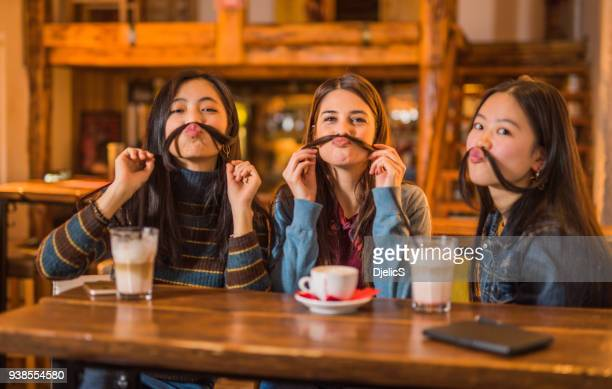 Three happy mixed race female friends joking around in cafe together.